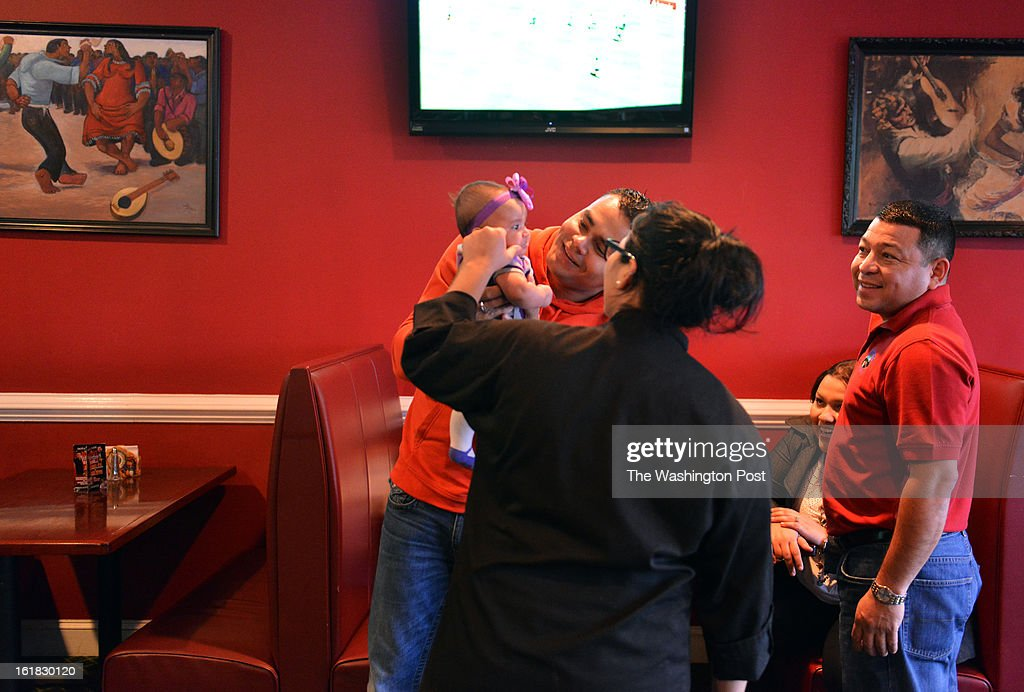 Jennifer Martinez, restaurant hostess and daughter of the owner, pinches the cheek of Montserrat Ruiz, 3 months, who is being held by her father Edwin Ruiz, of Woodbridge, at Dona (~ over the n) Tere Restaurant on Sunday, February 3, 2012, in Manassas, VA. The child's mother, Darsy Portillo, is seated 2nd from R next to restaurant owner Joel Martinez, R. Prince William County was a key battleground for immigration in the Washington area. Now the area is home to many working and middle class immigrants, both legal and not.
