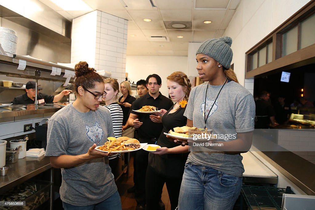 Jennifer O'Neill #0 and Reshanda Gray #21 of the Minnesota Lynx serve food during the Tip-A-Lynx fundraiser to benefit the Minnesota Lynx Fastbreak Foundation on June 3, 2015 at the Loop West End Bar & Restaurant in Minneapolis, Minnesota.