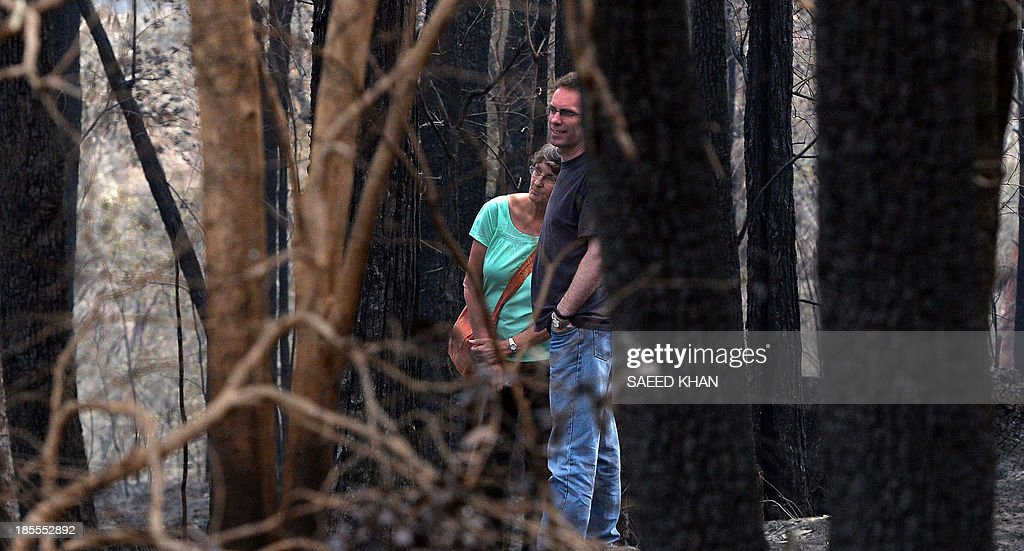 Jennifer Schweinsberg leans on her son David's shoulder as she walks in the backyard of her burnt house at Winmalee in the Blue Mountains on October 22, 2013. Jennifer visited her gutted house for the first time after spending four days in the hospital due to chest pain after seeing her burning house; she lost her property in the bushfire where she spend 40 years of her life with her two children. Firefighters on October 22 deliberately merged two major blazes in southeastern Australia in a desperate attempt to manage the advancing infernos ahead of weather conditions that authorities warn will be 'as bad as it gets'. AFP PHOTO/ Saeed KHAN