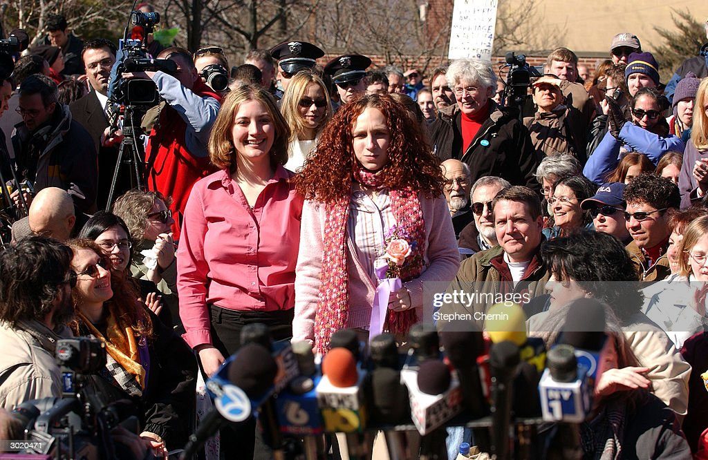 Jennifer Smits and her partner Dana Wegener walk down the aisle past onlookers and media before getting married outside village hall February 27 2004...