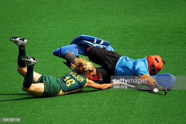 Jennifer Wilson of South Africa slides in to a challenge Petal Derry of Trinidad and Tobago during the women's hockey preliminary match between South...