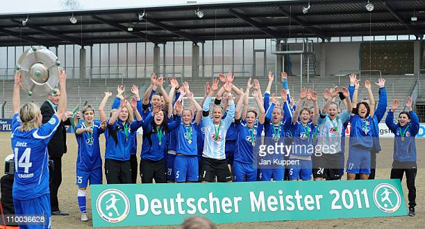 Jennifer Zietz of Potsdam holds up the trophy while her team mates celebrate after the Women Bundesliga match between Turbine Potsdam and...