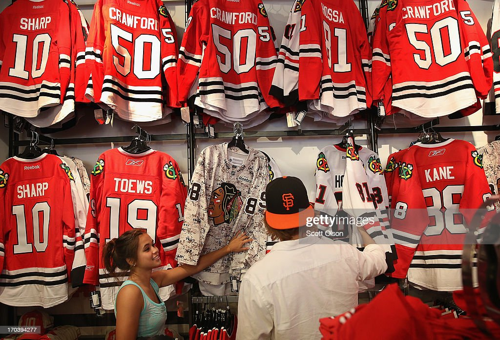 Jenny Ferguson (L) and Jeff Baude shop for merchandise in the Blackhawks Store on Michigan Avenue in the Loop on June 12, 2013 in Chicago, Illinois. The Chicago Blackhawks will match up against the Boston Bruins tonight at the United Center in the first game on the NHL Stanley Cup playoffs.
