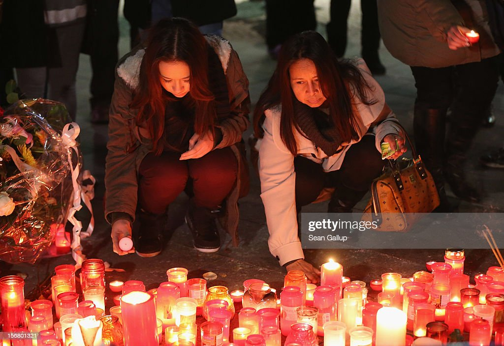Jenny K. (L) and Anong K., the younger sister and mother of Jonny K., light candles at a makeshift memorial to to Jonny following a memorial service for him and other victims of violence in Berlin at Alexanderplatz on November 21, 2012 in Berlin, Germany. Jonny K. died after a group of youths beat him severely in the early hours of October 14 at Alexanderplatz. Investigations are continuing as three of the suspects remain abroad, one in Turkey and two in Greece.