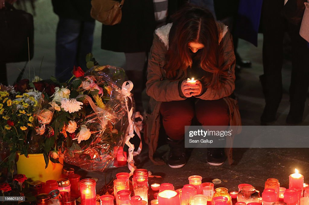 Jenny K., the younger sister of Jonny K., lights a candle at a makeshift memorial to her murdered brother following a memorial service for him and other victims of violence in Berlin at Alexanderplatz on November 21, 2012 in Berlin, Germany. Jonny K. died after a group of youths beat him severely in the early hours of October 14 at Alexanderplatz. Investigations are continuing as three of the suspects remain abroad, one in Turkey and two in Greece.