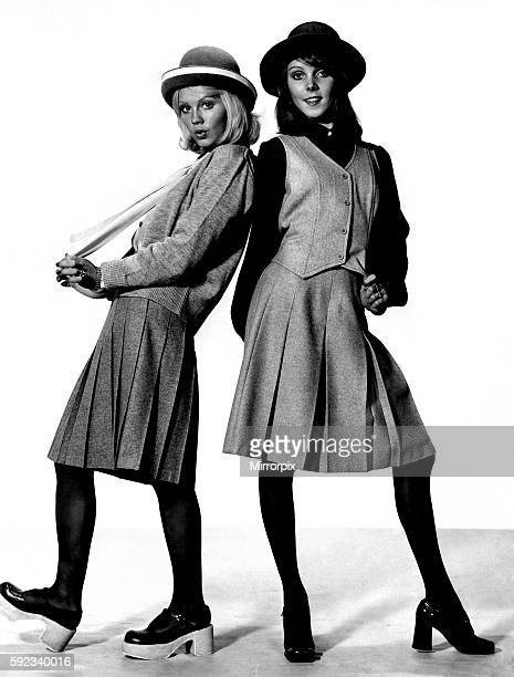 Jenny on the right wears a grey flannel pleated skirt price £799 grey wool cardigan £244 blue silkylook shirt £399 and grey bowler hat with white...