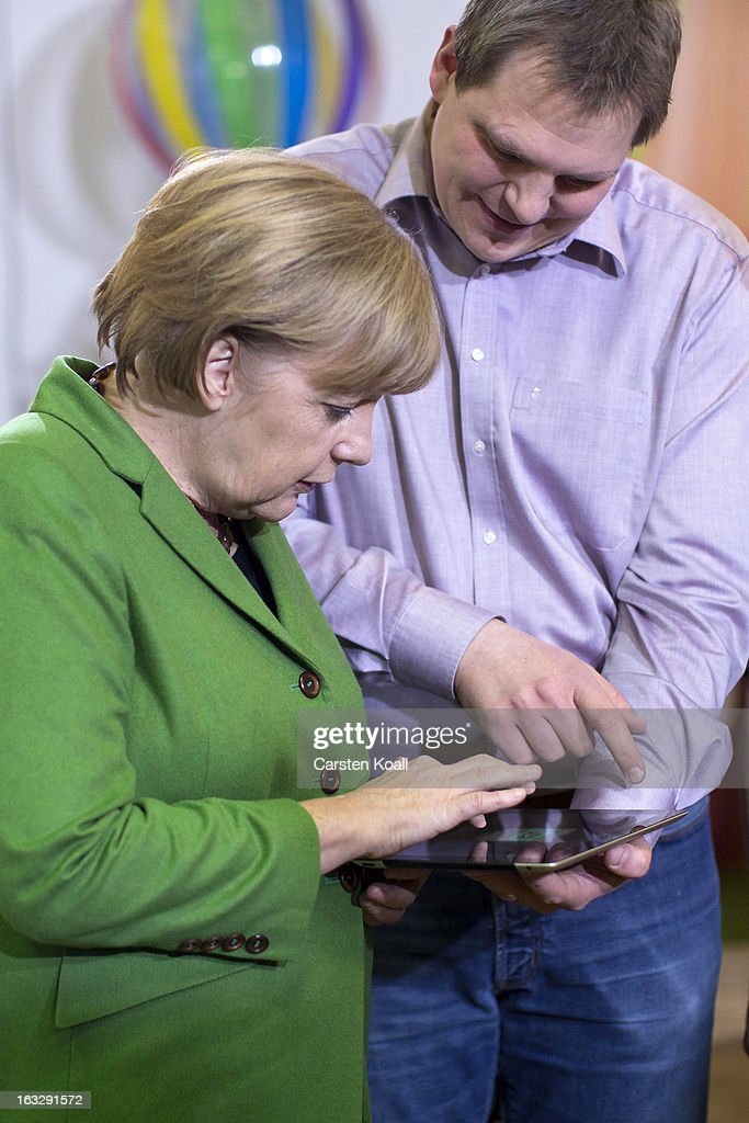 Jens Begemann (R), general manager of the Wooga company, explains German Chancellor Angela Merkel (L) a game on the tablet computer, during a visit in the Wooga company, which makes social games for smartphones and tablets on March 7, 2013 in Berlin, Germany. Berlin has drawn a significant number of startup companies in recent years, many of which are drawn by the city's hip reputation and its comparatively low cost of living.