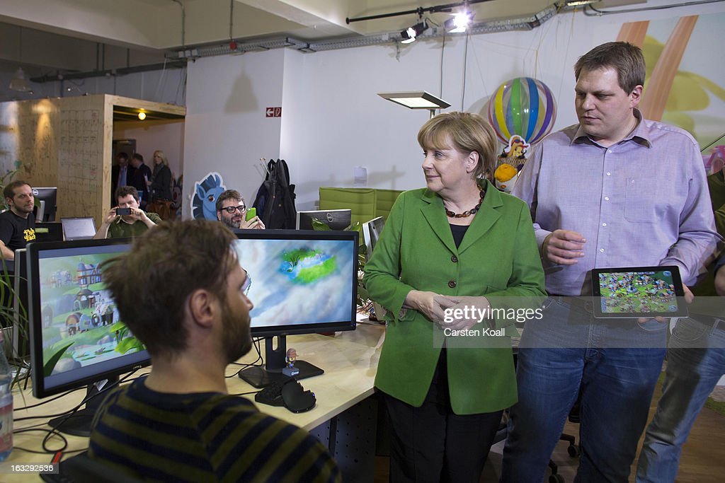Jens Begemann (R), general manager of the Wooga company, explains German Chancellor Angela Merkel (C) a game on the tablet computer, during a visit in the Wooga company, which makes social games for smartphones and tablets, on March 7, 2013 in Berlin, Germany. Berlin has drawn a significant number of startup companies in recent years, many of which are drawn by the city's hip reputation and its comparatively low cost of living.