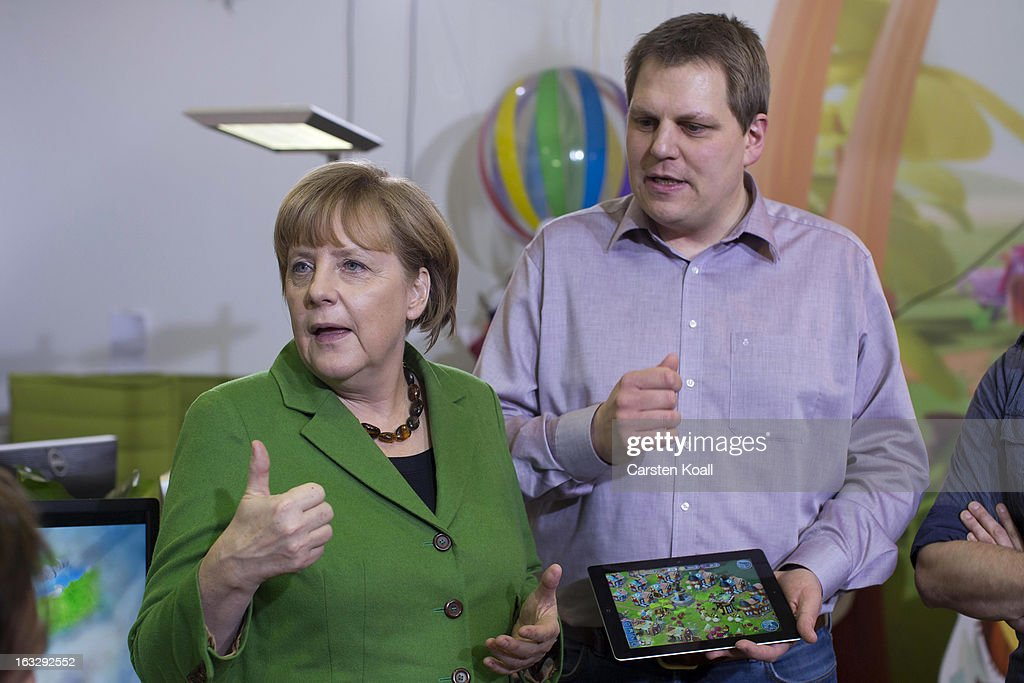 Jens Begemann (R), general manager of the Wooga company, explains German Chancellor <a gi-track='captionPersonalityLinkClicked' href=/galleries/search?phrase=Angela+Merkel&family=editorial&specificpeople=202161 ng-click='$event.stopPropagation()'>Angela Merkel</a> (C) a game on the tablet computer, during a visit in the Wooga company, which makes social games for smartphones and tablets, on March 7, 2013 in Berlin, Germany. Berlin has drawn a significant number of startup companies in recent years, many of which are drawn by the city's hip reputation and its comparatively low cost of living.