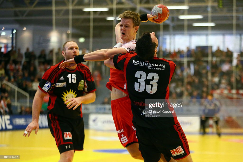 Jens Schoengarth of Tus N-Luebbecke (R) defends against Niclas Pieczkowski of TUSEM Essen (L) during the DKB Handball Bundesliga match between TUSEM Essen and Tus N-Luebbecke at the Sportpark Am Hallo on March 31, 2013 in Essen, Germany.