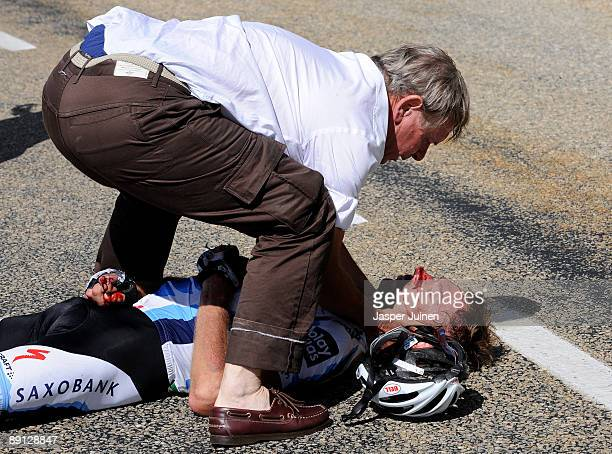 Jens Voigt of Germany and team Saxo Bank is attented to by his team's doctor after falling in the descend of the Col du PetitSaintBernard during...