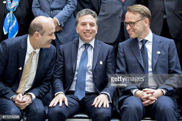 Jens Weidmann president of the Deutsche Bundesbank right speaks with Federico Sturzenegger president of the Central Bank of Argentina left and...