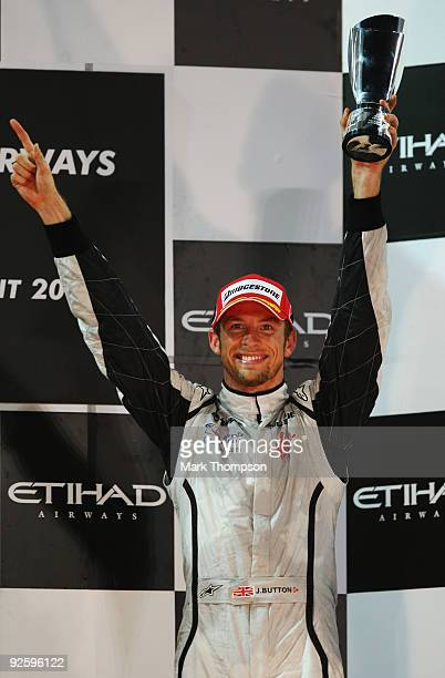 Jenson Button of Great Britain and Brawn GP celebrates on the podium after finishing third during the Abu Dhabi Formula One Grand Prix at the Yas...