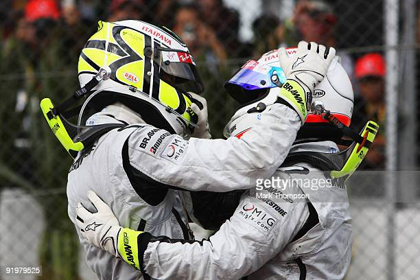 Jenson Button of Great Britain and Brawn GP is congratulated by team mate Rubens Barrichello of Brazil and Brawn GP as he celebrates in parc ferme...