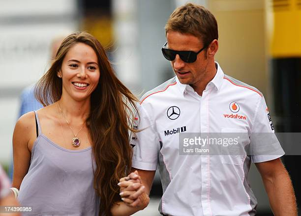 Jenson Button of Great Britain and McLaren and his girlfriend Jessica Michibata arrive in the paddock during previews to the Hungarian Formula One...