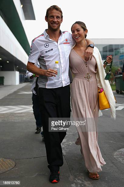 Jenson Button of Great Britain and McLaren and his girlfriend Jessica Michibata walk in the paddock following qualifying for the Indian Formula One...