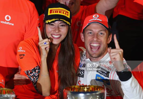 Jenson Button of Great Britain and McLaren celebrates in the pitlane with his girlfriend Jessica Michibata and team mates after winning the Japanese...