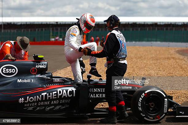 Jenson Button of Great Britain and McLaren Honda climbs out of his car after retiring in the Formula One Grand Prix of Great Britain at Silverstone...