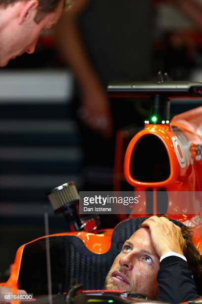 Jenson Button of Great Britain and McLaren Honda talks to a McLaren Honda team member during a seat fitting in the garage during previews for the...
