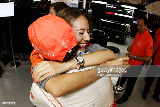Jenson Button of Great Britain and McLaren Mercedes celebrates in his team garage with his girlfriend Jessica Michibata after winning the Chinese...