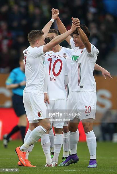 JeongHo Hong and Philipp Max of FC Augsburg celebrate their team's first goal during the Bundesliga match between FC Augsburg and Borussia Dortmund...