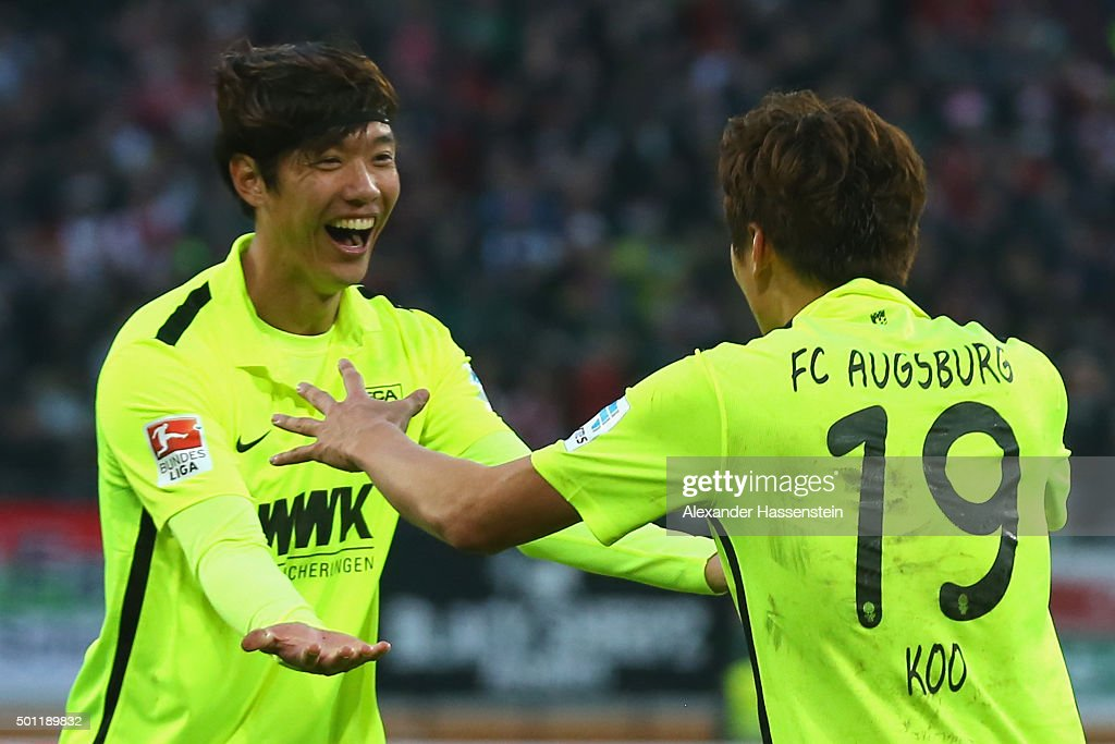 Jeong-Ho Hong (L) of Augsburg celebrates scoring the opening goal with his team mate Ja-Cheol Koo during the Bundesliga match between FC Augsburg and FC Schalke 04 at WWK Arena on December 13, 2015 in Augsburg, Germany.