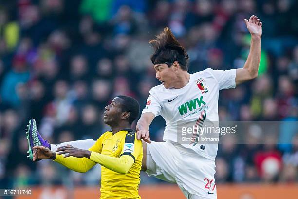 JeongHo Hong of Augsburg jumps for a header with Adrian Ramos of Dortmund during the Bundesliga match between FC Augsburg and Borussia Dortmund at...
