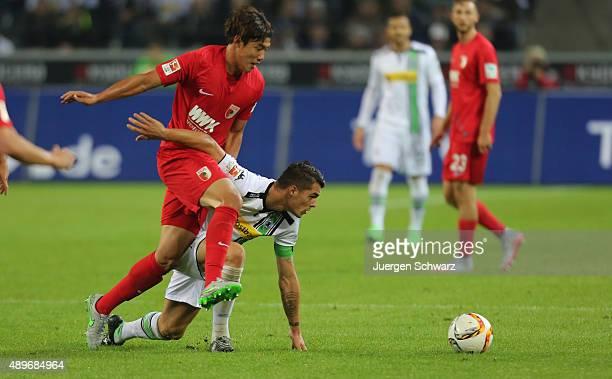JeongHo Hong of Augsburg tackles Granit Xhaka of Moenchengladbach during the Bundesliga match between Borussia Moenchengladbach and FC Augsburg at...