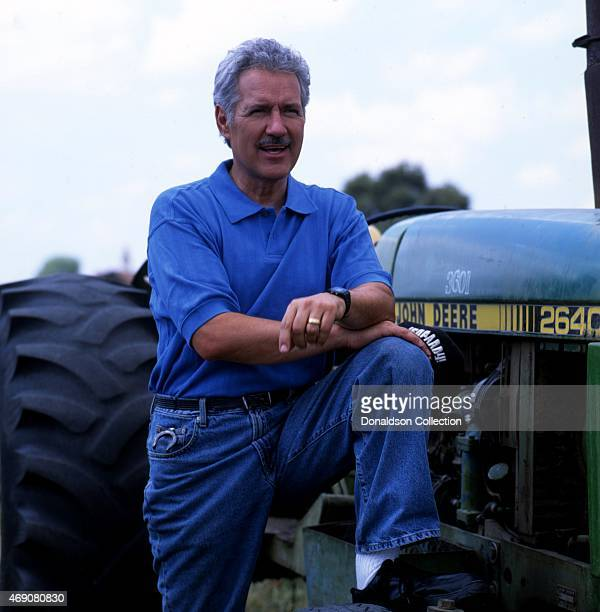 Jeopardy Game Show host Alex Trebek poses for a portrait sessio with a John Deere Tractor in 1997 in Los Angeles California