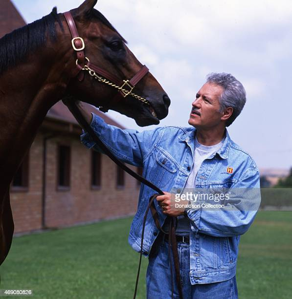 Jeopardy Game Show host Alex Trebek poses for a portrait session with a horse in 1997 in Los Angeles California