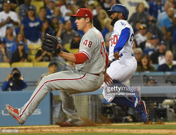 Jerad Eickhoff of the Philadelphia Phillies looks for the throw as Andrew Toles of the Los Angeles Dodgers heads for home as he scores on a passed...