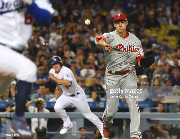 Jerad Eickhoff of the Philadelphia Phillies throws out Andrew Toles of the Los Angeles Dodgers at first base during the game at Dodger Stadium on...