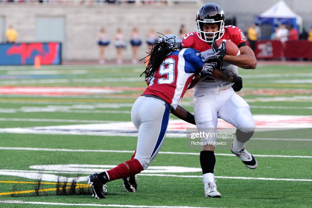 Jerald Brown #39 of the Montreal Alouettes stops Jon Cornish #9 of the Calgary Stampeders rushing during the CFL game at Percival Molson Stadium on July 13, 2013 in Montreal, Quebec, Canada. The Stampeders defeated the Alouettes 22-14.