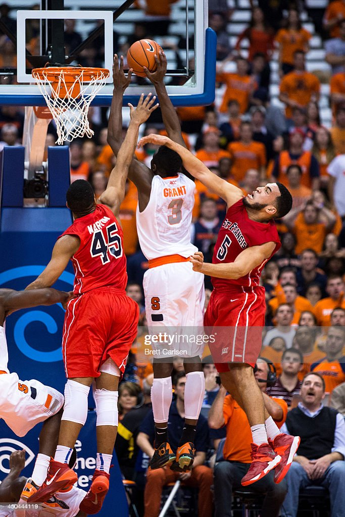 Jerami Grant #3 of Syracuse Orange puts in a field goal in the second half while defenders Wayne Martin #45 and Jalen Cannon #5 of St Francis Terriers reach in during a basketball game on November 18, 2013 at the Carrier Dome in Syracuse, New York. Syracuse wins 56-50.