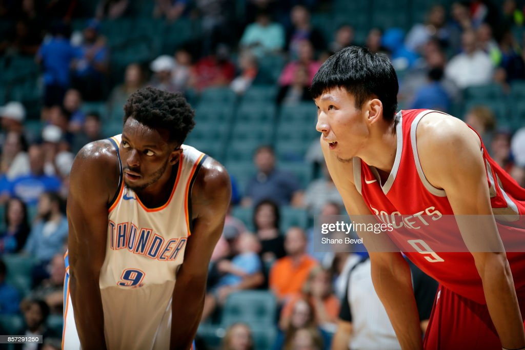 Jerami Grant #9 of the Oklahoma City Thunder and Zhou Qi #9 of the Houston Rockets react to a play during the preseason game on October 3, 2017 at the BOK Center in Tulsa, Oklahoma.