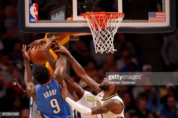 Jerami Grant of the Oklahoma City Thunder fights for a rebound against Paul Millsap and Will Barton of the Denver Nuggets at the Pepsi Center on...