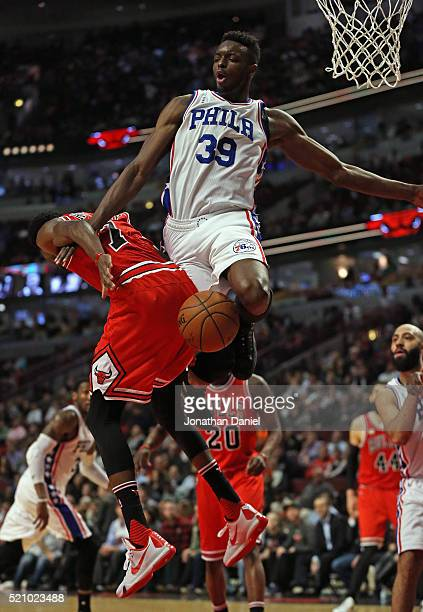 Jerami Grant of the Philadelphia 76ers fouls Justin Holiday of the Chicago Bulls at the United Center on April 13 2016 in Chicago Illinois The Bulls...