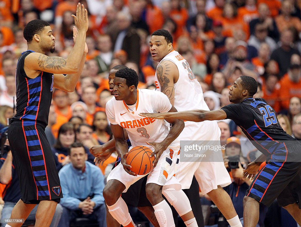 Jerami Grant #3 of the Syracuse Orange drives to the basket against Durrell McDonald #25 and Derrell Robertson #10 of the DePaul Blue Demons during the game at the Carrier Dome on March 6, 2013 in Syracuse, New York.