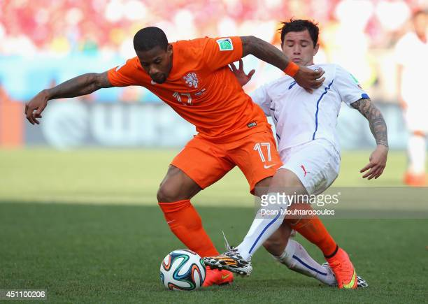 Jeremain Lens of the Netherlands and Eugenio Mena of Chile compete for the ball during the 2014 FIFA World Cup Brazil Group B match between the...