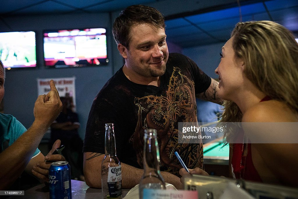 Jeremiah Constant, a drill equipment salesman originally from Colorado, flirts with Brittany Paige, originally from California at a bar on July 27, 2013 in Williston, North Dakota. The western region of North Dakota has seen a rise in crime, automobile accidents and drug usage recently, due in part to the oil boom which has brought tens of thousands of jobs to the region, lowering state unemployment and bringing a surplus to the state budget.