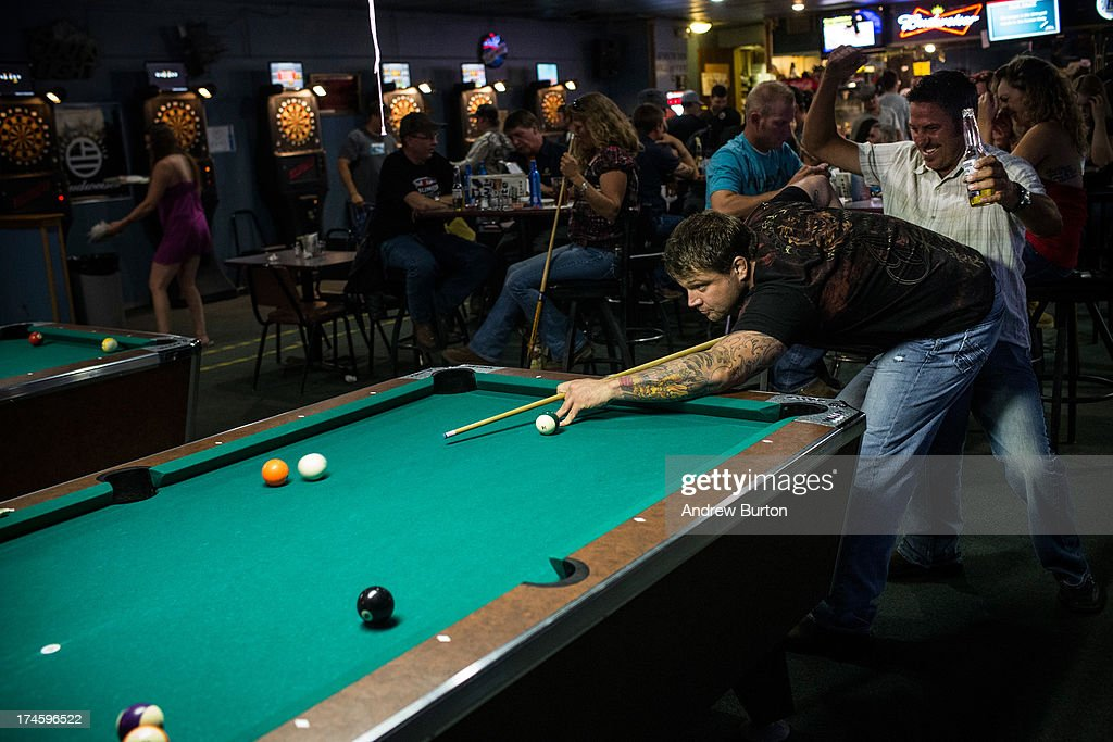 Jeremiah Constant, a drill equipment salesman originally from Colorado, plays a game of pool at a bar on July 27, 2013 in Williston, North Dakota. The western region of North Dakota has seen a rise in crime, automobile accidents and drug usage recently, due in part to the oil boom which has brought tens of thousands of jobs to the region, lowering state unemployment and bringing a surplus to the state budget.