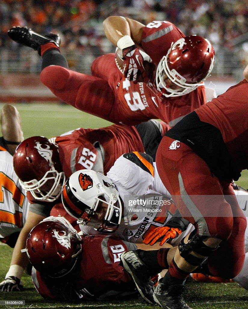 Jeremiah Laufasa #43 of the Washington State Cougars scores a touchdown against the Oregon State Beavers during the game at Martin Stadium on October 12, 2013 in Pullman, Washington.