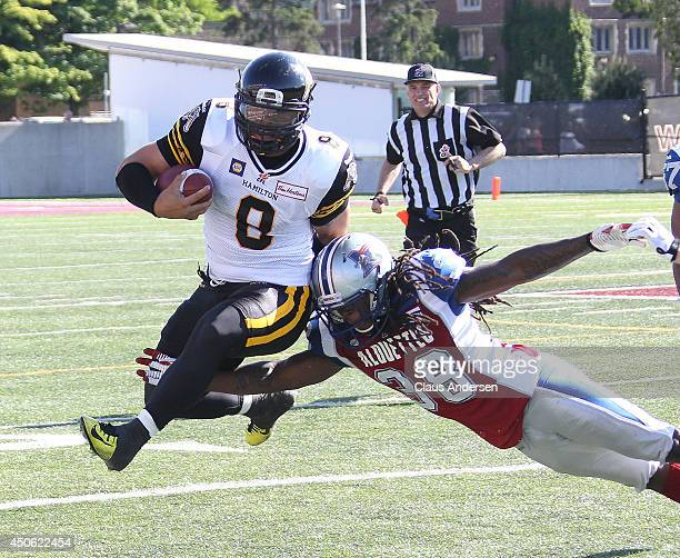 Jeremiah Masoli of the Hamilton TigerCats eludes a tackle by Dominique Ellis of the Montreal Alouettes in a preseason CFL football game at Ivor Wynne...