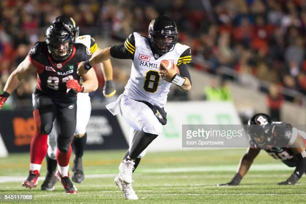 Jeremiah Masoli of the Hamilton TigerCats runs with the ball against the Ottawa Redblacks in Canadian Football League Action at TD Place Stadium in...