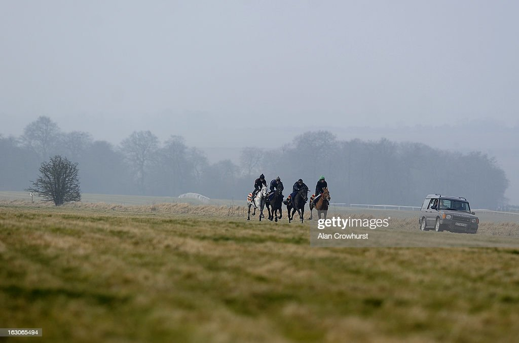 Jeremiah McGrath riding Simonsig (L) and David Bass riding Grandouet (2L) make their way up hill as trainer Nicky Henderson travels alongside in his vehicle on Lambourn gallops on March 04, 2013 in Lambourn, England.