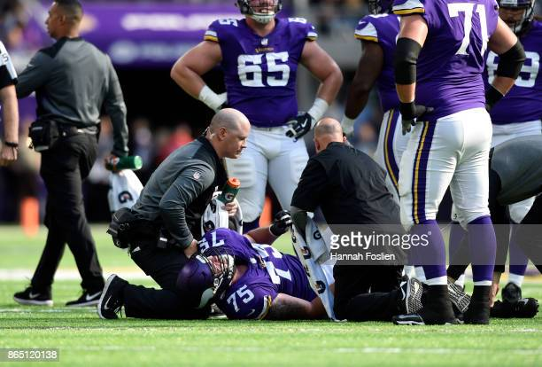 Jeremiah Sirles of the Minnesota Vikings is checked on by medical staff after suffering a knee injury in the first half of the game against the...