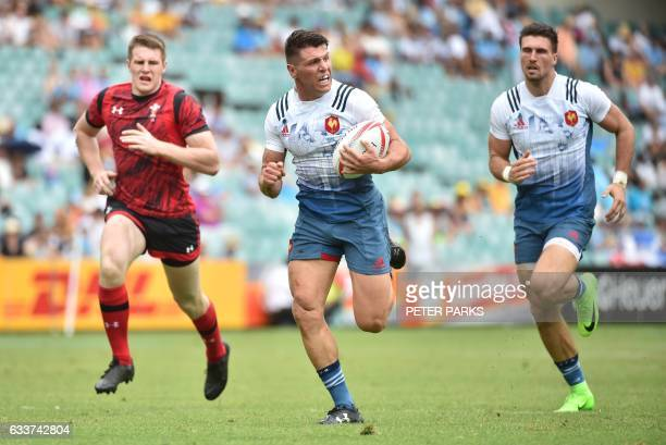 Jeremy Aicardi of France runs to score a try flanked by team mate Bastien Berenguel and Tom Williams of Wales in their pool B match at the Sydney...