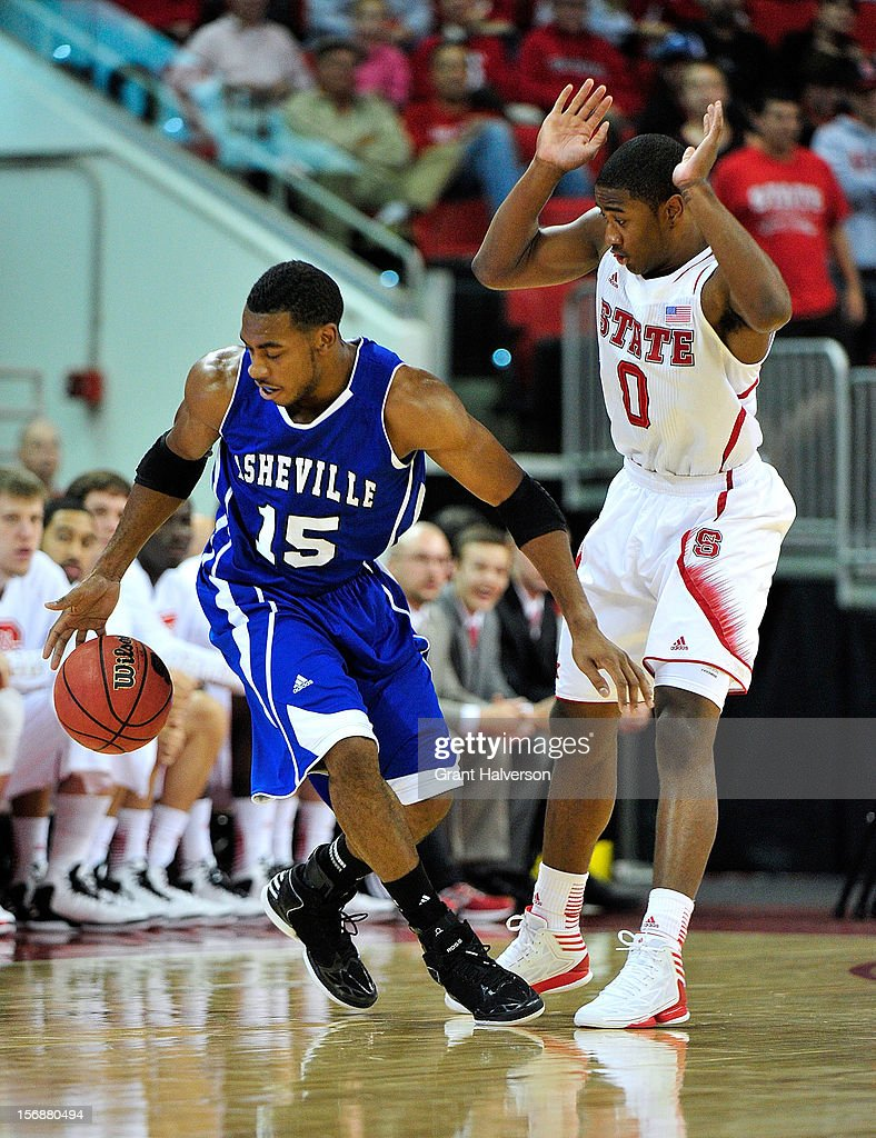Jeremy Atkinson #15 of the North Carolina-Asheville Bulldogs loses the ball as he collides with defender Rodney Purvis #0 of the North Carolina State Wolfpack during play at PNC Arena on November 23, 2012 in Raleigh, North Carolina.