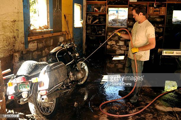 Jeremy Barnes rinse the motorcycle at the garage damaged by flooding waters at Altona in Boulder County Boulder Colorado September 25 2013