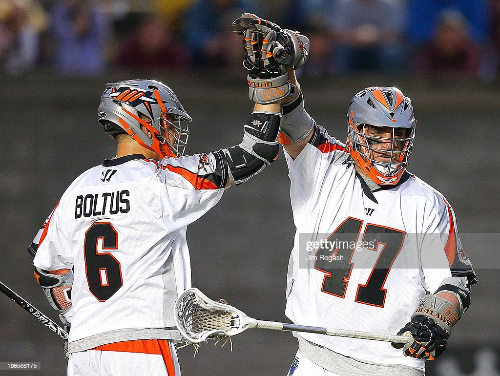 Jeremy Boltus #6 and Anthony Kelly #47 of the Denver Outlaws celebrate Kelly's goal against the Boston Cannon in the second quarter at Harvard Stadium on May 11, 2013 in Boston, Massachusetts.